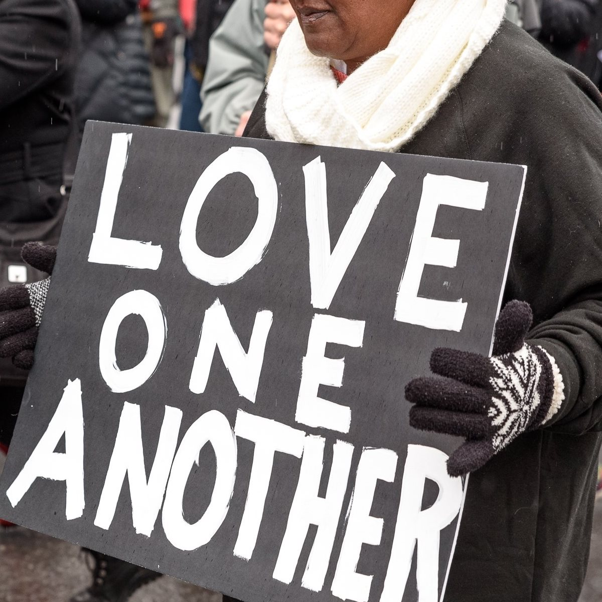 "A woman holding a sign that reads ""Love One Another"""